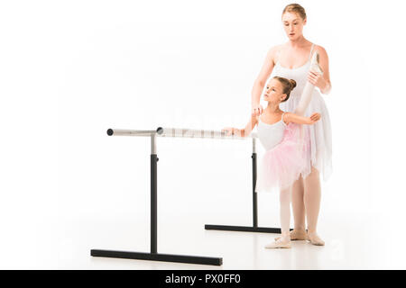 focused female teacher in tutu helping little ballerina practicing at ballet barre stand isolated on white background - Stock Photo