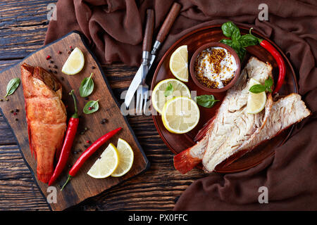 fillet of hot smoked red snapper served on a earthenware plate with fresh basil leaves, lemon slices, fork and knife on a wooden rustic table, view fr - Stock Photo