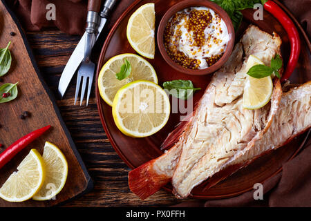 fillet of hot smoked red snapper served on a earthenware plate with fresh basil leaves, lemon slices and mustard sauce, fork and knife on a wooden rus - Stock Photo