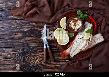fillet of red snapper served on a earthenware plate with fresh basil leaves, lemon slices and mustard sauce, fork and knife on a wooden rustic table,  - Stock Photo