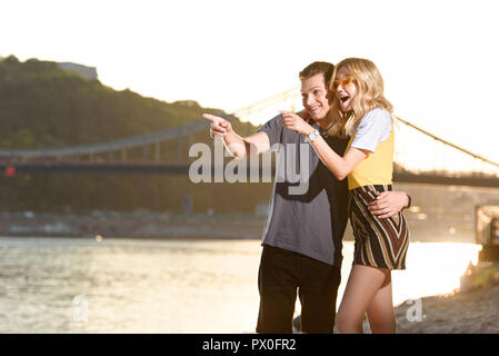 young couple pointing on something at river beach during sunset - Stock Photo
