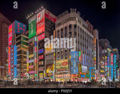 An evening shot in the heart of busy Shinjuku, Toyko, Japan at a busy crossing, with neon signs, the shopping district, neon billboard. - Stock Photo