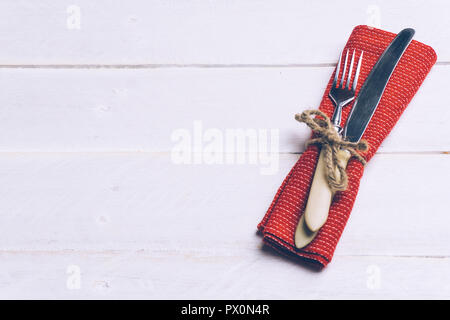 Holiday Christmas food background concept. Christmas table with a set of cutlery knife and fork on a red napkin with xmas decorations. White wood back - Stock Photo