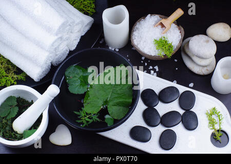Spa treatment kit with hot massage stones, bath salt and herbal extract for the skin. Green and white set. - Stock Photo