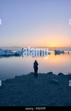 A photographer at Jokulsarlon glacier lagoon and icebergs in south east Iceland in the midnight sun. - Stock Photo