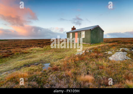 A tiny cottage or hut known as a shieling which is used for shelter while pasturing animals, on peat bog near Stornoway on the Isle of Lewis in Scotla - Stock Photo