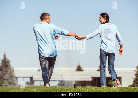 rear view of couple holding hands and dancing under automatic watering on green lawn near country house - Stock Photo