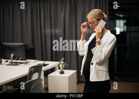 pregnant businesswoman in formal wear talking on smartphone in office - Stock Photo