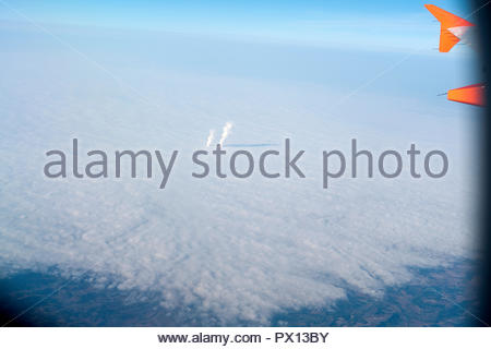 chimney exhaust pushed through the clouds seen from an airplane Europe France - Stock Photo