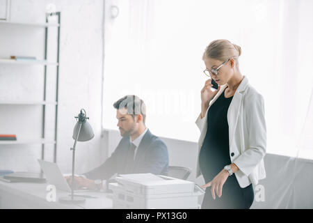 pregnant businesswoman talking on smartphone while colleague working on laptop at workplace in office - Stock Photo