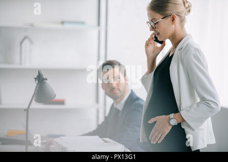 smiling pregnant businesswoman talking on smartphone while standing near colleague at workplace in office - Stock Photo