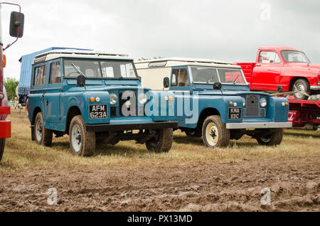 two old land rovers in a field - Stock Photo