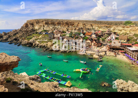 Beautiful view from the cliff with sea, hills, houses, people and beach. Popeye Village, Malta - Stock Photo