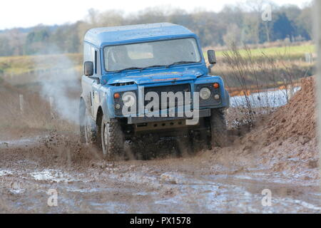 A Landrover rallying on a wet dirt track - Stock Photo
