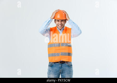 Disappointed handsome engineer wearing orange vest and jeans with helmet, isolated on white background - Stock Photo