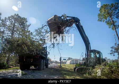 Seabees assigned to Naval Mobile Construction Battalion (NMCB) 11 remove debris from a road using an excavator at Naval Support Activity Panama City, Florida. NMCB-11 sent a 54-man, task-tailored Seabee detachment that includes, mechanics, electricians, equipment operators, builders, and administrative, logistics and culinary personnel in response to damage caused by Hurricane Michael. (U.S. Navy photo by Mass Communication Specialist 1st Class Collin Turner/released) - Stock Photo