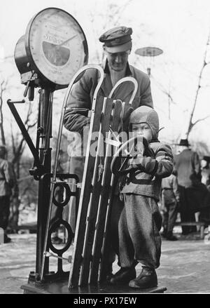 Sledge in the 1950s. A small child is standing on a scale together with the sled. Sweden 1950s. - Stock Photo