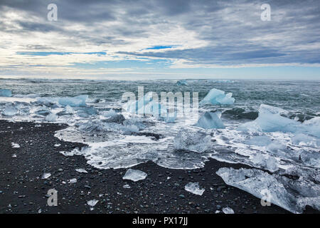 Diamond Beach, South Iceland, where ice from Jokulsarlon Glacial Lagoon is deposited on the volcanic black sand. - Stock Photo
