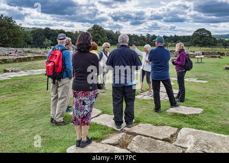 11 August 2018: Northumberland, UK - Visitors listening to a guide on a tour at Chesters Roman Fort, Hadrian's Wall, Northumberland, UK - Stock Photo