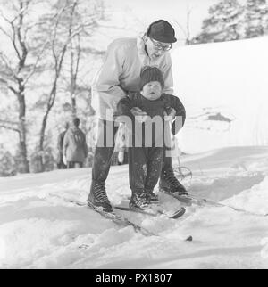 Winter in the 1960s. A father and his son are enjoying a winter day skiing. The boy gets some help to balance himself on the skis. It's a day of winter sport at Fiskartorpet in Stockholm February 1960. - Stock Photo