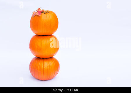 Tower of Three stacked mini pumpkins with fall maple leaf on the top on the white background isolated. Autumn holiday, harvest, Helloween concept. Sel - Stock Photo