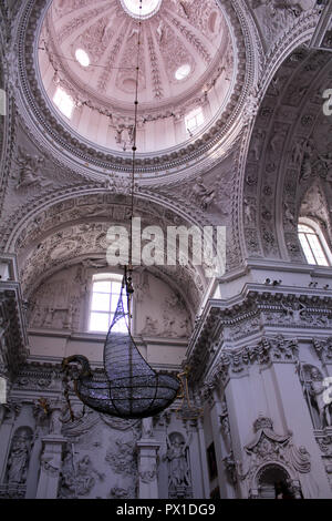 Highly ornate interior of Church of St. Peter and St. Paul, with tall dome and suspended fishing boat, in Vilnius, Lithuania - Stock Photo