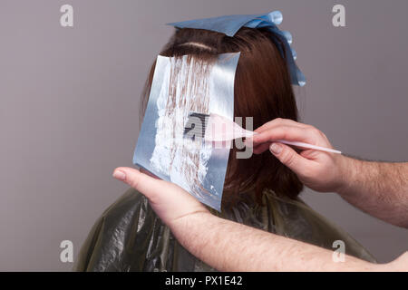 Professional hairdresser holding brush and dyeing hair of her client. studio shot. isolated on white background. - Stock Photo
