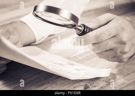 Businessman Checking His Documents With A Magnifying Glass, Monochrome Colors - Stock Photo