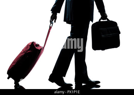 detail side view one caucasian business traveler man walking with suitcase  full length silhouette in studio isolated white background - Stock Photo