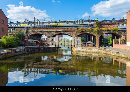 Metrolink tram on a Victorian railway viaduct, and a modern footbridge at Slate Wharf on the Bridgewater Canal at Castlefield, Manchester, England, UK - Stock Photo