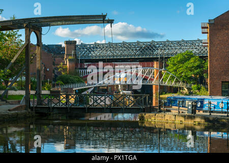 A bascule footbridge, the Merchants' Bridge and Victorian railway viaducts from the Middle Warehouse basin, Castlefield, Manchester, England, UK