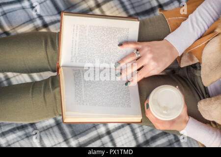 Woman with book on legs and coffee in hand. Girl reading book on retro blanket. Autumn concept image. Close up, selective focus - Stock Photo