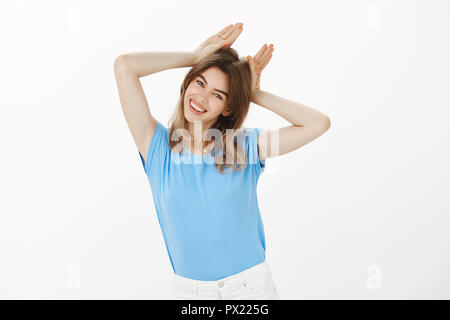 Girl mimicking kitten, being cute and adorable. Carefree feminine european female in blue t-shirt, tilting head right and smiling while holding palms on head as if it is animal ears, having fun - Stock Photo