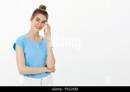 Cute female psychologist getting ready for next appointment. Happy good-looking european woman in glasses and bun, standing half-turned with crossed arm, touching rim of eyewear and smiling - Stock Photo