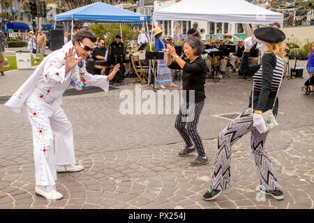 An Elvis impersonator, a mime in white makeup, and an Asian American woman dance on cobblestones at an outdoor music festival in Laguna Beach, CA. - Stock Photo
