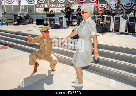 A World War II veteran in US Army uniform and a women dressed as a Red Cross volunteer happily dance the jutterbug at a Veterans Day celebration in Costa Mesa, CA. - Stock Photo