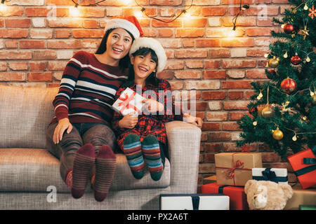 joyful mom and child sitting on the couch celebrating xmas together in living room. cute little girl holding gift showing big toothy smile. many gifts - Stock Photo