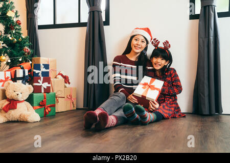 Kid with gift from lovely mom. happy christmas decoration in the house. attractive girl childhood and young mother sitting on the wooden floor face to - Stock Photo