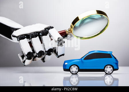 Robot Examining Blue Car With Magnifying Glass - Stock Photo