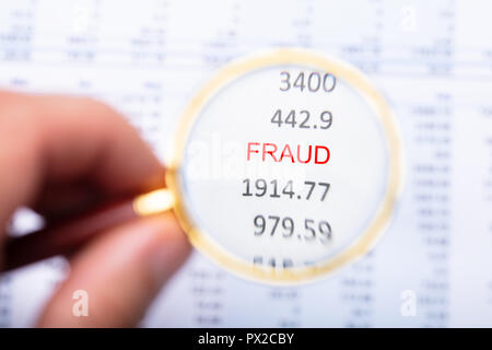 Man's Hand Examining Fraud Word On Financial Report Through Magnifying Glass - Stock Photo