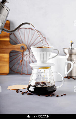 Pour over coffee being made with a kettle and glass carafe with hot water being poured - Stock Photo
