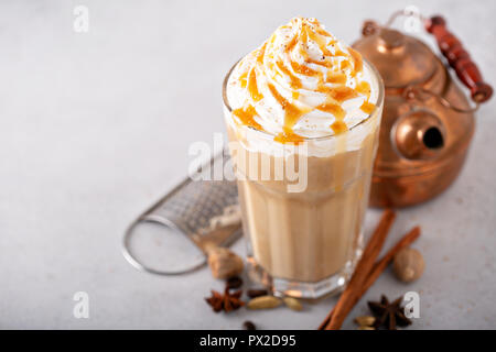 Spiced iced chai latte with whipped cream, seasonal fall drink - Stock Photo