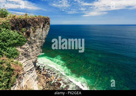 Man standing with raised hands on the cliff with amazing ocean and cloudy sky view - Stock Photo
