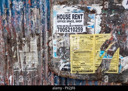 Advertising posters on side of fence, Shillong, Meghalaya, India - Stock Photo
