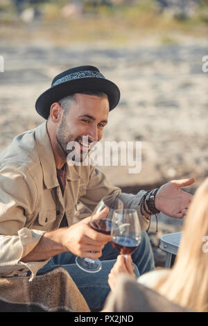 happy couple clinking with glasses of wine during a picnic - Stock Photo