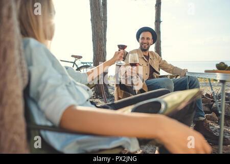 young couple clinking with glasses of wine during picnic - Stock Photo