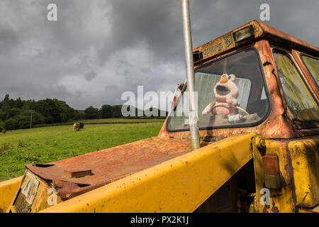 Furry toy posed to drive old mechanical digger on farm, Wales, UK - Stock Photo