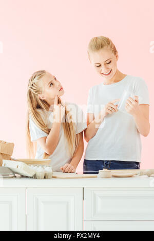 beautiful mother and daughter in white t-shirts cooking together isolated on pink - Stock Photo