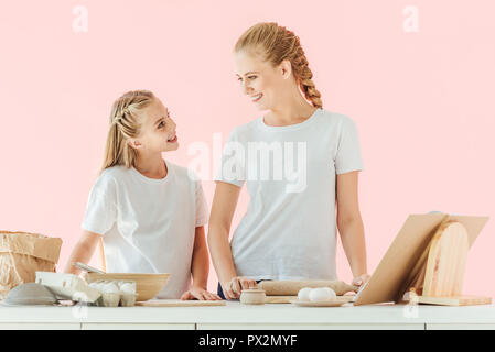 smiling mother and daughter in white t-shirts looking at each other while cooking together isolated on pink - Stock Photo