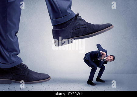 Young handsome businessman getting crushed by a big formal shoe  - Stock Photo